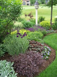 *Beautiful curved flower bed with birdhouse.