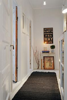 White lets you breathe easier in a narrow hallway. I like the minimalism, contrast, and inspiring quote :)