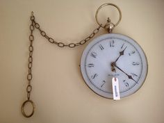 HANGING FRENCH CLOCK. HAS THE APPEARANCE OF A POCKET WATCH. 22H X 13W