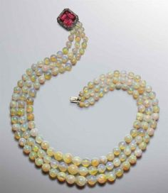 AN ATTRACTIVE OPAL AND TOURMALINE NECKLACE The necklace composed of three rows of graduated opal beads measuring from 13.1mm to 5.8mm to the early Art Deco clasp mounted with a square-shaped pink tourmaline surrounded by millegrain-set rose-cut diamonds,clasp circa 1915, necklace 50.0cm long, longest strand 56.5cm, shortest strand 47.5cm