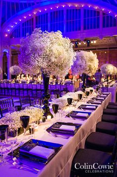 A chic mixture of high and low arrangements of gypsophila are accented by black lacquer floral vessels and dinnerware