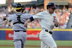 Atlanta Braves' Phil Gosselin scores past Oakland Athletics catcher John Jaso (5) on a Freddie Freeman double during the first inning of a baseball game.