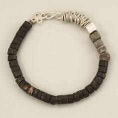 Bracelet of Pyrite disks with matted texture, combined with silver plates folded like paper and a single silver cube l Agas & Tamar Design, Israel