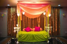 Vibrant green and peach mehendi setup with fuchsia pillow covers adorned with crystal side lamps! Adorable wedding decor <3
