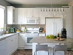 kitchens - Ralph Lauren - Mombasa Mist - Zodiac Quartz Countertop DWR Brushed Aluminum Bent Plywood Barstools Z Gallerie Casablanca Lantern Z Gallerie Linear Strand Crystal Chandelier Pottery Barn Museum Craft Collection - Shelburne Museum Pom-Pom Geometric Runner Lewis Dolin Decorative Hardware Inc. Bar Pull Collection - Bar Knobs gray walls white glass-front kitchen cabinets kitchen island