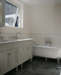 Ett lyxigt badrum med karaktär och vintagekänsla. Golvet täcks av grå marmor och på väggarna kombineras vit träpanel med matt, vitt kakel. Rummet är smakfullt möblerat med ett fristående badkar på silverfärgade tassar och ett lyxigt dubbelhandfat i marmor. Vit, Bathroom Toilets, Double Vanity, Inspiration, Biblical Inspiration, Inspirational, Double Sink Vanity, Inhalation