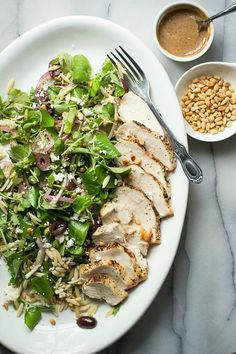 A healthy watercress orzo salad with pine nuts, olives, cheese and grilled chicken
