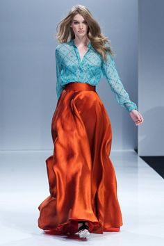 Flowing long maxi skirt in hammered satin that is a glowing-amber color. Paired with a turquoise blouse that has copper accents. Designer: Alexander Terekhov. Source: Russian Vogue.