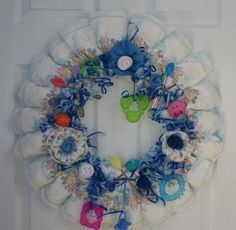 How to make a diaper wreath: Attach diapers and other baby items to a coat hanger to make a baby wreath. Unique gift for an expectant mother.  Read more: http://www.craftelf.com/Party_Favors_Diaper_Wreath.htm#ixzz2VaxQaa7p