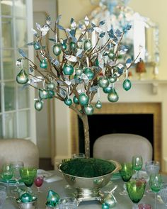 Martha's fantastical tree, hung with gleaming teal and mint-green apples and pears, is the focal point for a holiday table at Martha's East Hampton, New York, house. The branch is embedded in a large, heavy floral frog, placed in an antique footed bowl, surrounded with green floral foam (oasis), and covered with moss. Polystyrene fruits are wrapped in mint- and teal-green metallic leaf, and they are tied to the branches with silver ribbon. Delicate silver leaves, which are glued to the…