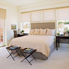 This master bedroom packs a lot of style in a not-so-big space. A headboard upholstered in outdoor fabric with a sophisticated herringbone stripe spans the wall behind the bed. Simple, pleated Roman shades dress the windows; long curtain panels would overwhelm the space.
