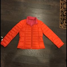 Down Jacket - Coral Orange in Color Orange Down Jacket - weighs next to nothing and packs up into a teeny tiny little roll! Size Small. No idea what the dark parts are, but I tried to photograph them. These are very faint and I have not tried getting them out. Bernardo Jackets & Coats