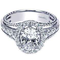 14K White Gold Oval Halo Diamond Engagement Ring with Rope Detail. This unique ring features .69cttw of round diamonds bead set, tapering down the shank and in an oval shaped halo accenting a 1ct oval