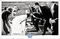 Bride and groom kissing prior to playing football at the Pro Football Hall of Fame in Canton, Ohio. By Corey Ann Photography