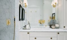A neutral and marble bathroom with gold hardware