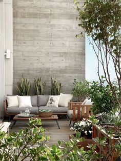 Give your apartment balcony some edge with the white and gray color scheme. The touch of gray brick walls in contrast to the white walls also give out a good charisma. The potted plants and white flowers are also great addition to the overall theme.