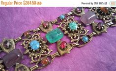 Vintage Unsigned Selro Red Green Purple Gold Rhinestone Chunky Wide Bracelet - Retro 1950s 1960s- High End Hard To Find Jewelry offered by MartiniMermaid on etsy  Style: Retro 60s High End Designer style  Color: gold tone metal with cabs & rhinestones in turquoise, lavender, amber, blue, red, purple, and green Bracelet approximate Size: 8 x 2  Condition: Very good Approximate Date: 1950s - 1960s Hallmarks/signature: Unsigned but attributed to Selro  Stunning statement jewelry that i...