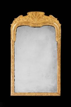 QUEEN ANNE PERIOD GILT WOOD MIRROR  A Queen Anne period gesso and gilt wood Pier Mirror, the surface carved with shells and scrolls and with a continuously etched border, replacement period plate.  c. 1720 to c. 1725