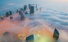This breathtaking view from the Burj Khalifa, the world's tallest building, shows a thick blanket of smoggy fog smothering Dubai. The mist almost completely covers the skyscrapers which dominate the skyline. Picture: Bjoern Lauen/Solent News