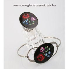 Magyaros motívumú karkötő, mely gyönyörűen megmunkált. Festett virágminták és 4 db Swarovski kristály található a karkötőben. A kristályok nagysága 3 mm. A karkötő nemesacél foglalatban található, mely nem kopik le. Hozzá illő Magyaros motívumú gyűrű, mely gyönyörűen megmunkált. Festett virágminták és 4 db Swarovski kristály található a gyűrűben. A kristályok nagysága 3 mm.