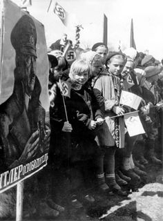 "Belarusian children waving German flags by a picture of Hitler that says in Russian ""Hitler, the Liberator"". This photograph was taken on 1 May 1944 during a parade of Germans and Belarusians in Minsk, Belarus."