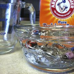 How to (Easily!) Clean Silver Jewelry. Line the bottom of a small bowl with foil. Lay the jewelry  on the foil. The silver must be in contact with the foil. Sprinkle about a teaspoon of baking soda over the silver. Pour very hot (almost boiling) water into the bowl. Let sit until cool (at least 10 minutes).