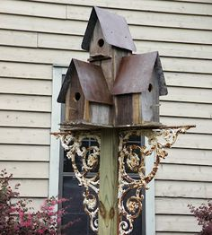 birdhouses on a post with wrought iron gingerbread pieces. This would be a great use of one of our 20 fence posts that will never become a fence.
