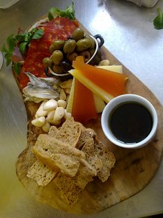 This is a tapas board, Serrano Ham, Chorizo, Marcona Almonds, Olives, Marinated Anchovies, Pickled Garlic, Manchego, Membrillo, Balsamic Sherry Vinegar and Olive Oil, Home Made Bread.    All these products come from Brindisa in London who import directly from Spain.