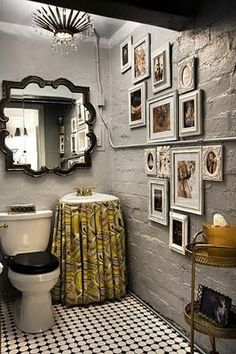 Love the non-traditional shape of the mirror and the skirt covering the small sink.  The grey on grey decor with black accents makes this small bathroom comfortable looking. messyjessiolson