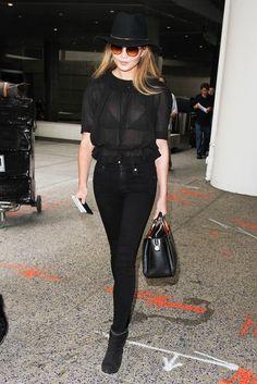 Chrissy Teigen steps out in a black sheer short sleeve top, black skinny jeans, black ankle boots a structured black bag, hat and sunglasses.