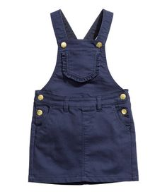 Dark blue. Pinafore dress in soft stretch twill with adjustable straps with press-studs, a chest pocket with a frilled edge, front and back pockets and