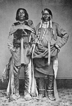 Sappix and son were Ute Indians. Both in native dress, one with face paint and ornaments, one holding bag. Photograph 1869