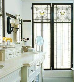 Stained-glass windows, original to the master bath of this 1920s home, play a big role in the remodeled version and brighten a neutral color scheme.