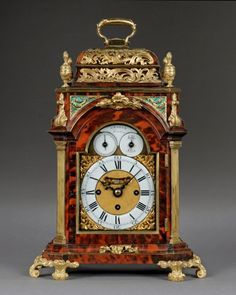 GRAHAM, London c1760 An exquisite small tortoiseshell and ormolu mounted quarter striking bracket clock. The red tortoiseshell veneered case, with canted corners, is profusely ordained with fine ormolu mounts. The break arch brass dial has corner spandrels and an enamel chapter ring. Within the arch are two subsidiary dials flanking a plaque with the maker's name. The subsidiary dials indicate the day of the month and strike/silent option.