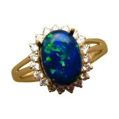 A Black Opal ring with an oval Black Opal and a halo of quality Diamonds in 14k Gold.