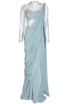 Featuring a frost blue ruffled saree gown in crepe and tulle base with layers of pearl, sequins and glass moti embellishments forming conceptual sand impression artwork on the saree pallu. Bollywood Designer Sarees, Latest Designer Sarees, Designer Dresses, Drape Sarees, Saree Gown, Indian Fashion Designers, Black Saree, Stylish Dress Designs, Stylish Sarees