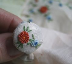 way to use embroidered (but stained) vintage linens... thumbtacks, magnets, buttons, more