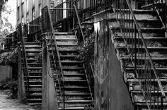 A black and white photo of some old creepy stairs.