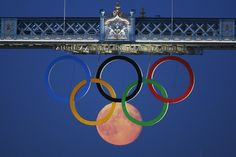 (Reuters) The full moon rises behind the Olympic rings on Tower Bridge, London. Aug. 3rd 2012