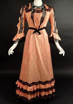 Circa 1905 Salmon and White Cotton Dress. The bodice has a square cut neckline trimmed in black lace. Pin tucks and gathers down the center front. Pin tucks fall from either side of the neckline to the waist. Long, set in sleeves fall with lace insets and pin tucks to below the elbows and end with a gathered flounce. Black velvet ribbon circles the waist of the bodice. Gored skirt falls from a narrow waistband with black lace and two tiers of ruffles along the bottom skirt.