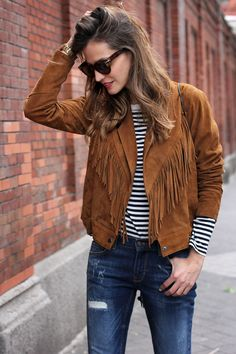 A suede fringe jacket can be dressed up or down. Layer it over a striped tee and jeans for a casual feel.