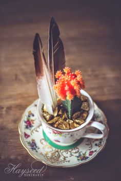 Sweet creative touches: cactus, meets feathers, meets gold foil rocks (I'm sure), and teacup with saucer   Hayseed Homemakin'