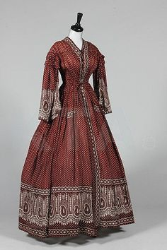A printed cotton day dress, circa with small red paisley motif repeats, fan-pleating from waist to shoulders, bust approx together with a paisley-print deshabille the wine coloured ground with white paisley borders Vestidos Vintage, Vintage Gowns, Vintage Outfits, Victorian Gown, Victorian Fashion, Vintage Fashion, Antique Clothing, Historical Clothing, 1850s Fashion