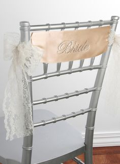 Bride Satin Chair Sash  Decorate the chairs at your event with a beautiful combination of glamour and delicate lace. This satin ribbon chair sash is double sided for a finished and elegant look. Customize the sash by choosing the satin and lace color. Bride is written in sparkling rhinestones to compliment the elegant design. Perfect for bridal showers and weddings, these chair sashes bring a dazzling look to any event.  Also available: Bridesmaid, Maid of Honor, Matron of Honor, Flower…