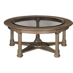 Thomasville's round Lonestar Cocktail Table has a one-inch beveled tempered glass top that reveals a distinctive star feature beneath. The frame and legs are fashioned in a warm, taupe-colored oak finish with off white cerusing. The stretcher features a s