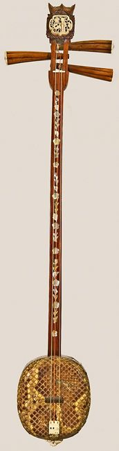 Sanxian, China, ca. 1850. Long-necked lute. Three strings. Bent, wooden neck; resonator covered with python skin. Carved ivory tailpiece. Peghead plaque depicts garden scene. Hand-carved bat effigies on peghead and endpiece.