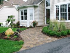 A wide, curved paver walkway and plantings create a much more welcoming entrance