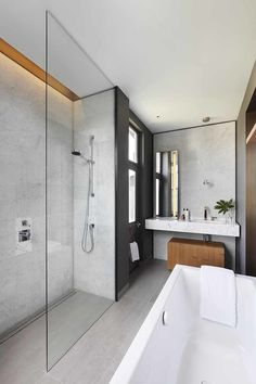 The adjoining master bathroom is connected by mirrored pocket door with bronze trim at the frame. The graphic space features a Kaldewei tub, Domus tiles, and Dornbracht faucets and fixtures. A marble vanity top and medicine cabinet sit against the far wall; a compact wood bench slides smartly under the vanity.
