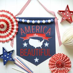 """America the Beautiful BannerSize: Large 14"""" x 17""""*PRE ORDER NO CUSTOMIZATION*{B a n n e r  C o l o r s}Canvas: Navy BlueVinyl color: White, Red, Pale BlueFelt Balls: White, DenimRibbon: Red and White Stripe{P r o d u c t   D e t a i l s}Materials: Canvas Fabric, Heat press vinyl, Bakers twine, Ribbon, Pine dowelBanners are made of a heavy canvas material and topped stitched on all sides. Vinyl is cut using the best heat press vinyl mater..."""