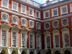 Courtyard inside Hampton Court, England. Cardinal Thomas Wolsey, favorite of King Henry Vlll, took over the site of Hampton Court Palace in 1514, and rebuilt the existing manor house to form the nucleus of the present palace. After falling out of the King's favor in 1528, the palace was passed on to Henry, and within six months of coming into ownership, the King began his own rebuilding and expansion. Henry's court consisted of over 1,000 people while the King owned over 60 houses and…